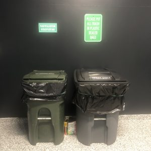 Rental trash and recycling bins in the garage by the wall